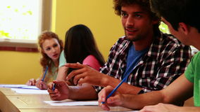 Students sitting in a line writing and chatting in classroom Royalty Free Stock Photos