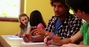 Students sitting in a line writing and chatting in classroom Royalty Free Stock Images