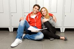 Students sitting by lockers Stock Images