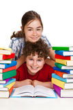 Students and pile of books. Students sitting next to pile of books Stock Image