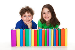 Students and pile of books. Students sitting next to pile of books Royalty Free Stock Photo