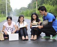 Students sitting on the road and sharing notes. Stock Photo