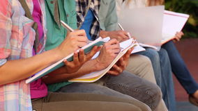 Students sitting in a row writing in notebooks Stock Photo