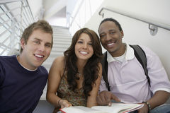 Students Sitting On Staircase With Book. Portrait of happy multiethnic college students sitting on staircase with book Royalty Free Stock Image