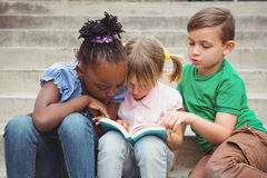 Students sitting on steps and reading a book. On the elementary school grounds Stock Image