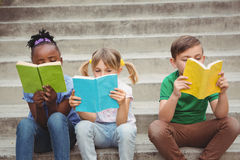 Students sitting on steps and reading books Stock Photo