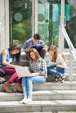 Students sitting on steps studying Stock Images