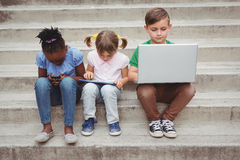 Students sitting on steps and using a tablet. On the elementary school grounds Stock Image
