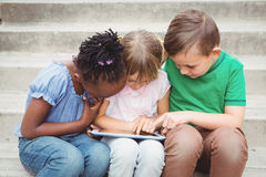 Students sitting on steps and using a tablet. On the elementary school grounds Stock Photos