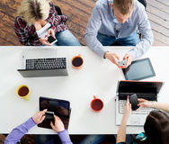 Students sitting at the table using computers and tablets Stock Photo