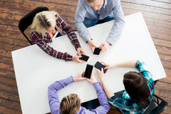 Students sitting by the table using smartphones Royalty Free Stock Photo