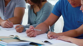 Students sitting together in front of notebooks stock footage
