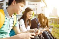 StudentsÂ-Sitzen und Anwendung des intelligenten Telefons stockfoto