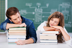 Students Sleeping On Stack Of Books Against Chalkboard. Male and female students sleeping on stack of books against chalkboard in classroom Royalty Free Stock Photo