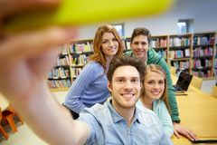 Students with smartphone taking selfie in library Stock Photos