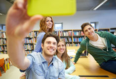 Students with smartphone taking selfie in library Royalty Free Stock Image
