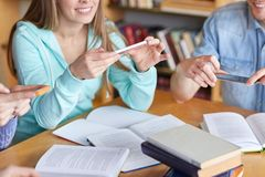 Students with smartphones making cheat sheets Royalty Free Stock Photos