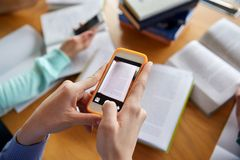 Students with smartphones making cheat sheets Royalty Free Stock Image