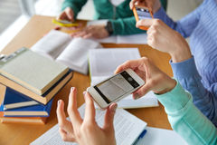 Students with smartphones making cheat sheets Royalty Free Stock Photography