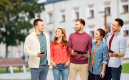 Students with smartphones and tablet computer. Technology, education and people concept - group of smiling friends or students with smartphones and tablet stock image