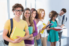 Students smiling at camera standing in a line. At the college Stock Image