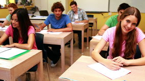 Students smiling and giving thumbs up to camera in classroom Royalty Free Stock Photo