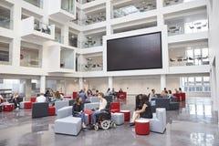 Students socialising under AV screen in atrium at university Stock Photos