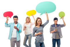 Students with speech bubbles and gadgets Royalty Free Stock Photo