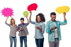Students with speech bubbles and gadgets Stock Photos