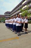Students stand in line. Students stand in line with the school building as a backdrop Stock Photos