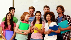 Students standing in classroom giving thumbs to camera Stock Images