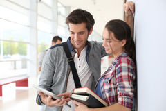 Students standing in hallway holding books Royalty Free Stock Photos