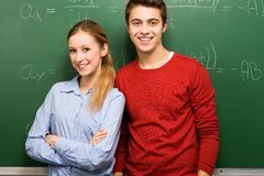 Students standing next to blackboard Stock Photo