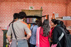 Students standing at open bookcase with rare editions of books during the Jaipur Literature Festival Royalty Free Stock Photography