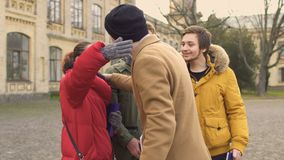 Students meets their friend near university. Students stands at the background of university. People are talking and waiting their colleague. Handsome guy comes stock video footage
