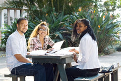 Students study together. Three young afircan college students sitting by a table outdoors near classroom building and study books and discussing about their Royalty Free Stock Photography