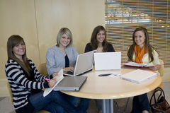 Students studying. A study group of attractive female college students studying on their laptop computers and reading their notes royalty free stock images