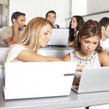 Students studying with laptops in class room Royalty Free Stock Image