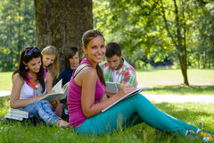 Students studying on meadow in park teens royalty free stock photo