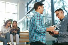 Students Studying, Reading Educational Information In College. Students Studying, Reading Educational Book In College. Young People Discussing Notes On Stairs Royalty Free Stock Images
