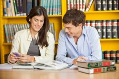 Students Studying At Table Against Bookshelf In Royalty Free Stock Photos