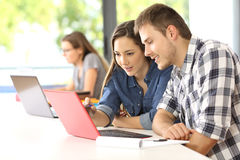 Students studying together in a classroom. Two concentrated students studying on line together sitting in a desktop in a classroom with a classmate in the Stock Photos