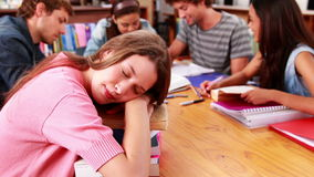 Students studying together in the library with girl sleeping on books stock footage