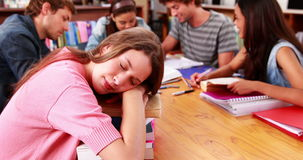 Students studying together in the library with girl sleeping on books stock video footage