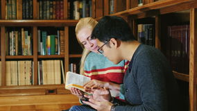 Students studying together in the library. Korean man and Caucasian woman stock footage