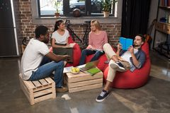 Students studying together. Multiethnic students with copybooks and books studying together at home Royalty Free Stock Photos
