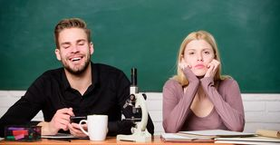 Students studying university. Genetics and engineering. Difficult university subject. Scientific experiment. Guy and. Girl at desk with microscope. Studying in stock photos