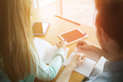 Students with tablet pc writing to notebooks Royalty Free Stock Images