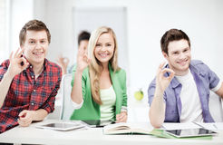 Students with tablet pcs showing ok sign Royalty Free Stock Photo