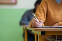 Students taking exam in classroom. Education test. Students taking exam in classroom. Education test and literacy concept. Cropped shot, hand detail Royalty Free Stock Photo